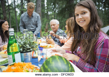 Portrait of girl having meal with family at campsite - Stock Photo