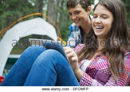 Siblings watching digital tablet at campsite - Stock Photo