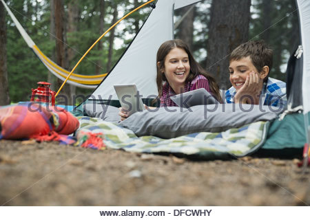 Happy siblings with digital tablets in tent at campsite - Stock Photo