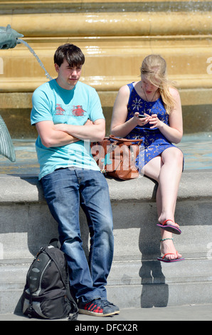 London, England, UK. Young couple (? no MR) by a fountain, girl on her phone, boy waiting - Stock Photo
