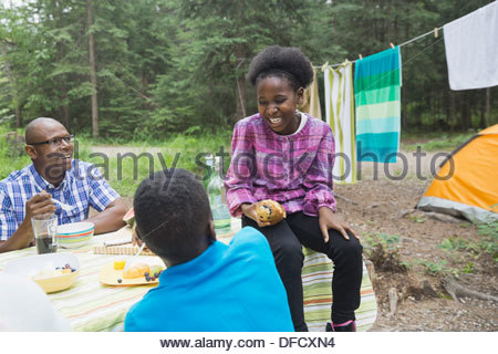 Happy children and father enjoying meal at campsite - Stock Photo