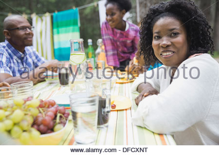 Portrait of smiling woman sitting with family at campground table - Stock Photo