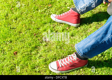 Legs of a young adult relaxing on grass. Mobile phone in hand - Stock Photo