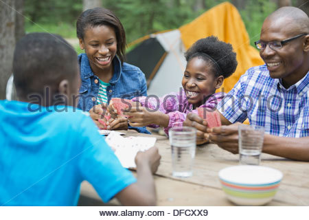 Cheerful family of four playing cards at campground - Stock Photo