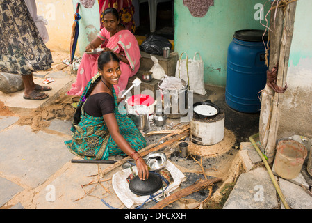Indian woman cooking dosa for people outside a rural village house. Andhra Pradesh, India - Stock Photo