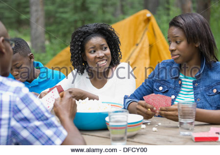 Family of four playing cards while camping - Stock Photo