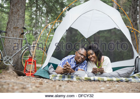 Portrait of happy couple lying in tent at campsite - Stock Photo