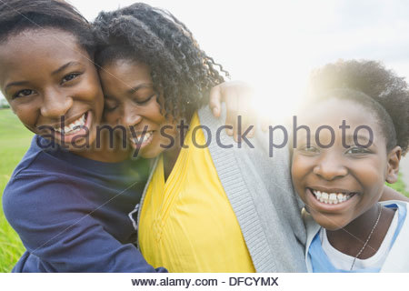 Portrait of happy daughters embracing mother outdoors - Stock Photo