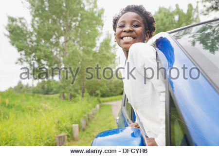 Cheerful girl looking out of car window - Stock Photo