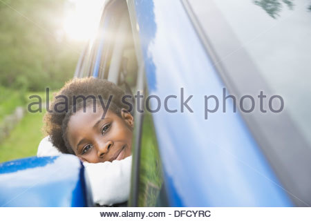 Portrait of girl looking out of car window - Stock Photo