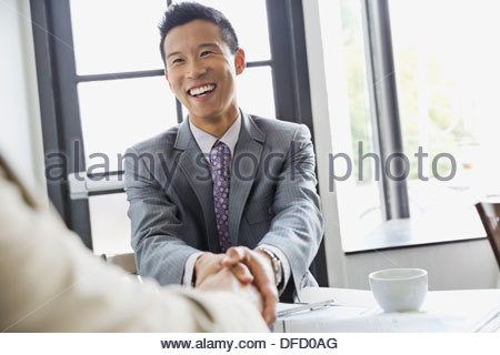 Businessman shaking hands with partner in restaurant - Stock Photo