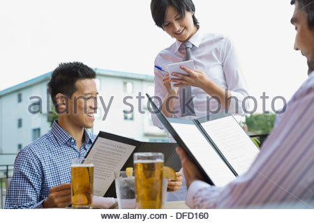Waitress taking order from businessmen at outdoor cafe - Stock Photo
