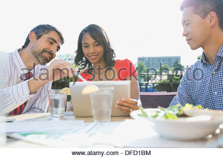 Business people using digital tablet at outdoor cafe - Stock Photo