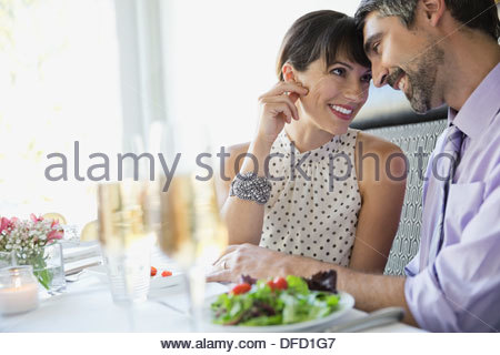 Affectionate couple sitting in restaurant - Stock Photo