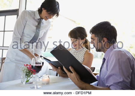Waitress taking order from professional couple in restaurant - Stock Photo