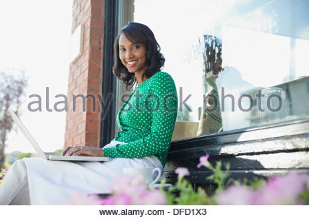 Portrait of woman with laptop sitting outside cafe - Stock Photo
