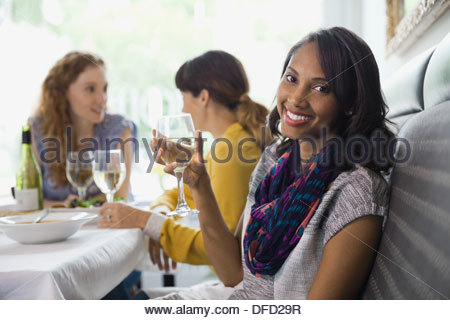 Portrait of smiling woman holding wineglass in restaurant - Stock Photo