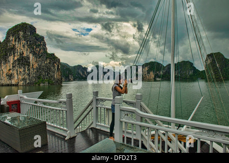 photographer on a junk in Halong Bay, Vietnam - Stock Photo