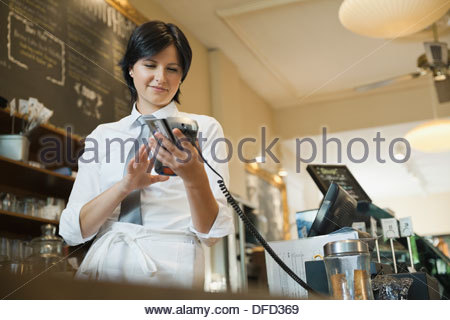 Waitress using credit card terminal in cafe - Stock Photo