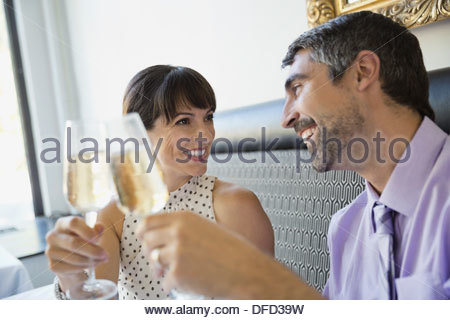 Professional couple toasting to each other with champagne - Stock Photo