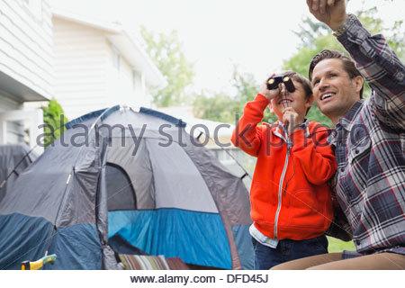 Little boy looking through binoculars in backyard - Stock Photo