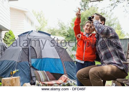 Father and son using binoculars in backyard - Stock Photo