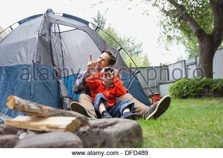Boy looking through binoculars with father in backyard - Stock Photo