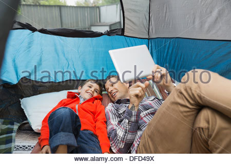 Father and son using digital tablet in tent - Stock Photo