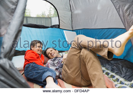 Smiling father and son using digital tablet in tent - Stock Photo