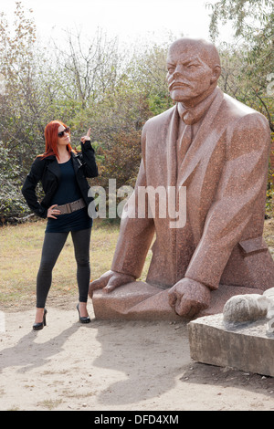 Hungarian woman pointing finger at statue of Lenin while visiting Memento Statue Park in Budapest, Hungary - Stock Photo