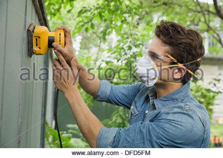 Man sanding down fench planks - Stock Photo