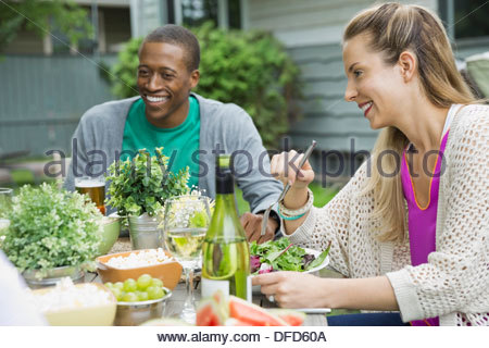 Friends enjoying meal at outdoor dining table - Stock Photo