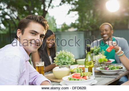 Portrait of smiling man having meal with friends at outdoor dining table - Stock Photo
