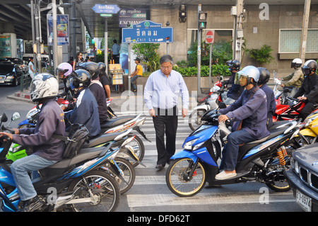 Bangkok (Thailand): a man trying to cross the street on a zebra crossing taken by motor-bikes in the Chit Lom area - Stock Photo