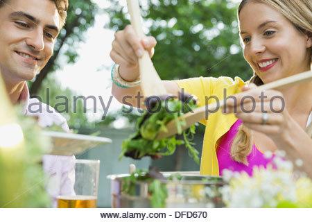 Woman serving salad to husband - Stock Photo