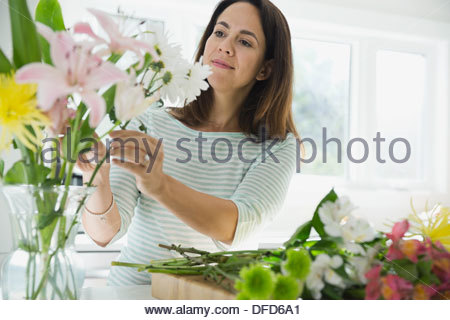 Woman arranging flowers in vase at home - Stock Photo