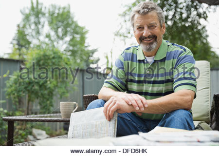Portrait of happy senior man holding newspaper while sitting in yard - Stock Photo