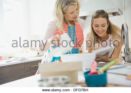 Mother and daughter reading recipe while baking in kitchen - Stock Photo