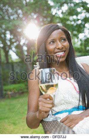 Happy woman with wineglass sitting in yard - Stock Photo