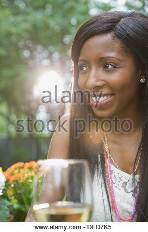 Smiling woman with wineglass sitting in yard - Stock Photo