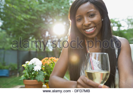 Portrait of smiling woman holding wineglass in yard - Stock Photo