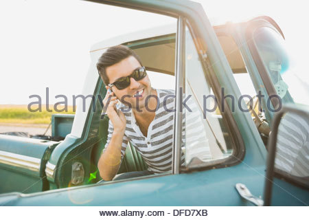 Man talking on smart phone in pick-up truck - Stock Photo