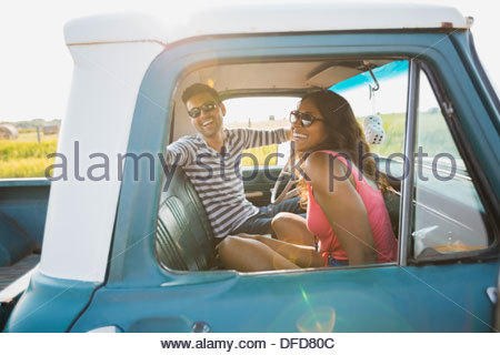 Cheerful young couple sitting in pick-up truck - Stock Photo