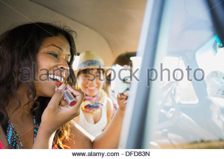 Woman applying lipstick using mobile phone in pick-up truck - Stock Photo