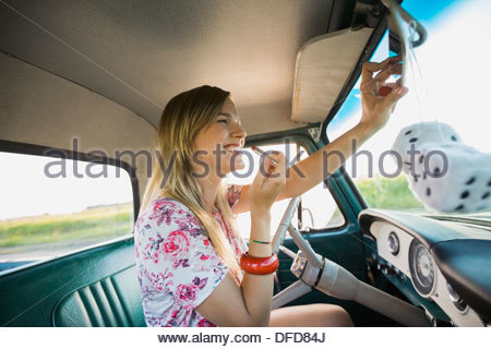 Woman applying lipstick in pick-up truck - Stock Photo