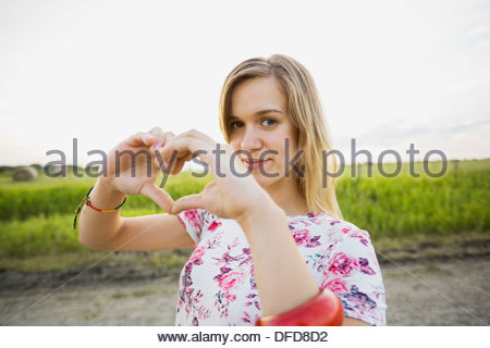 Portrait of beautiful woman making heart sign with hands - Stock Photo