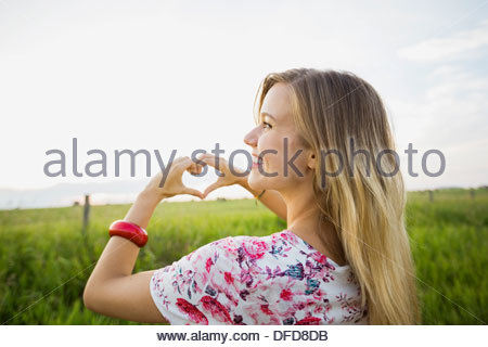 Over the shoulder view of young woman making heart shape with hands - Stock Photo