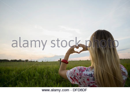 Rear view of woman framing heart with hands against sky - Stock Photo