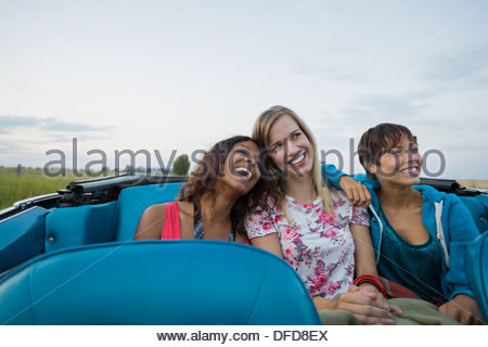 Smiling female friends sitting in convertible - Stock Photo