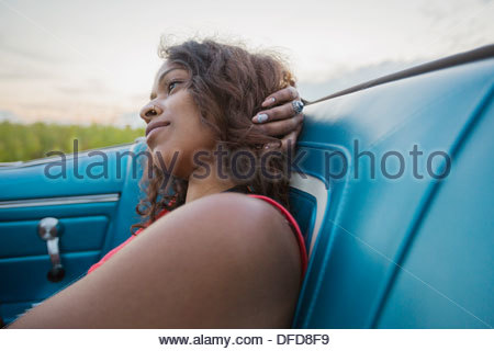 Thoughtful young woman sitting in convertible - Stock Photo